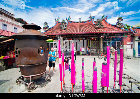 Malaysian people praying behind large incense sticks at a Buddhist temple in George Town, Penang, Malaysia, Southeast - Stock Photo