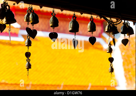 Close up of prayer bells, silhouetted against the colourful roof at Wat Doi Suthep, Chiang Mai, Thailand, Southeast - Stock Photo