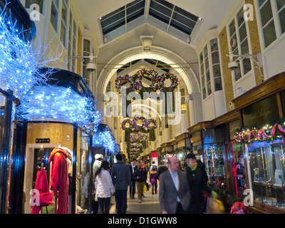 Burlington Arcade in Piccadilly with traditional Christmas decorations and shoppers with shopping bags London UK - Stock Photo
