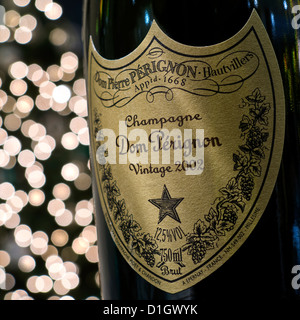 Bottle of exceptional year 2002 Dom Perignon luxury vintage champagne with sparkling lights in background - Stock Photo