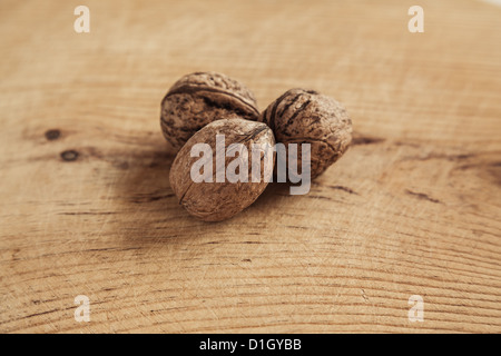 Three walnut on wooden background. Shallow depth of field. - Stock Photo