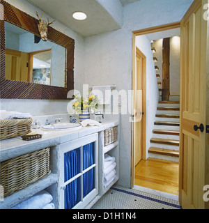 BATHROOM View rustic wood stairway through open door on right White open cabinets on left with wicker baskets holding - Stock Photo