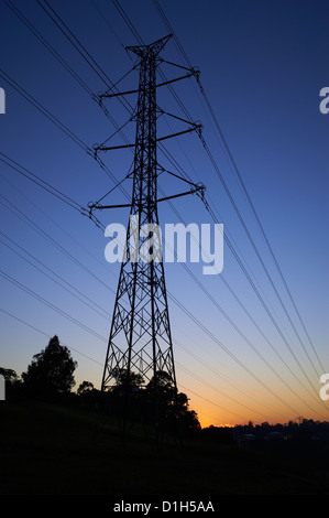 Silhouetted high voltage electricity pylon - Stock Photo