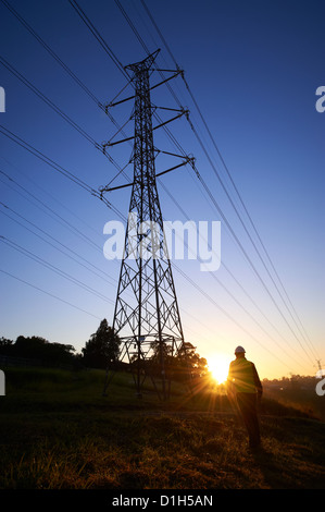 Silhouetted electricity pylons and worker in hard hat - Stock Photo