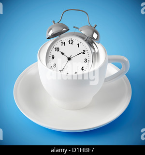 silver alarm clock in the white cup on blue background - Stock Photo