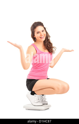 A happy female on a weight scale gesturing with her hands isolated against white background - Stock Photo