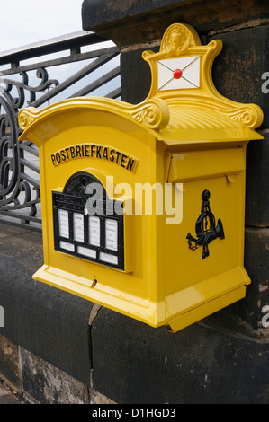 An old yellow post box (Postbriefkasten) in Altstadt, Dresden, Saxony, Federal Republic of Germany. - Stock Photo