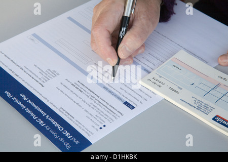 Close up Grandmother completing application for grandchild's investment plan - Stock Photo