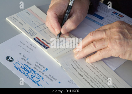 Close up pensioner writing cheque to pay oil heating bill - Stock Photo