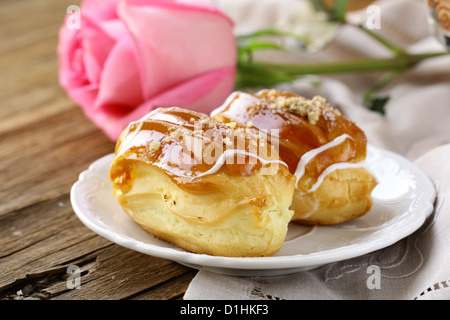 cakes eclair profiteroles on a plate - a dessert for two - Stock Photo