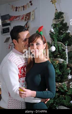Young couple in 20s celebrating Christmas by their decorated tree at home Photograph taken by Simon Dack 2012 - Stock Photo