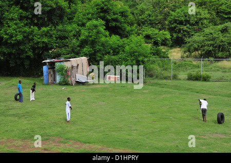 Four West Indian boys playing cricket in casual clothes on grass, Progress Park Cricket Ground, Grenville, Grenada, - Stock Photo