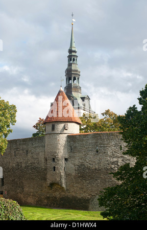 View of St. Nicholas' Church steeple and part of the wall of the old town in Tallinn, the capital of Estonia. - Stock Photo