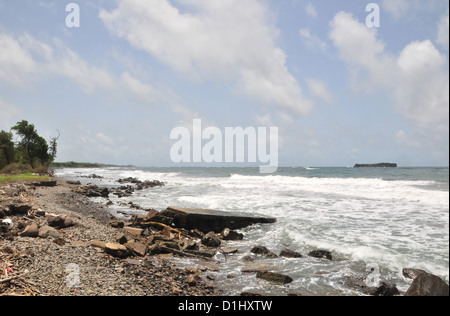 Blue sky white clouds coastal beach view, rocks. concrete, white surf, looking north from Pearls Airport, Grenada, - Stock Photo