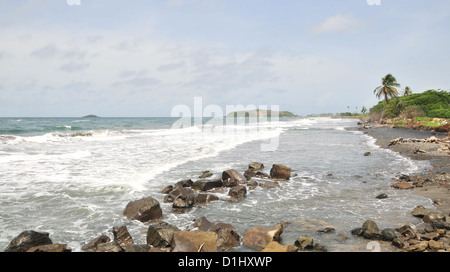 Sunny coastal view, south to Telescope Point, white surf, black beach sand, palm trees, at Pearls Airport, Grenada, - Stock Photo