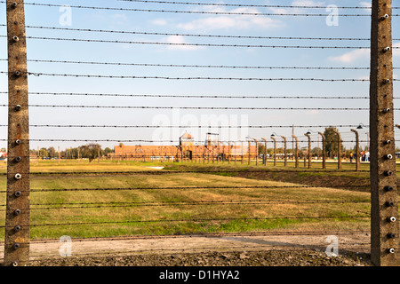 Barbed-wire fencing and buildings at the museum of the former Auschwitz II–Birkenau concentration camp in southern - Stock Photo