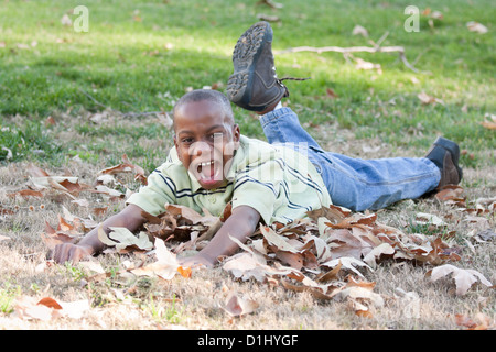 Young Handsome African American Boy Playing in the Park Among the Leaves. - Stock Photo