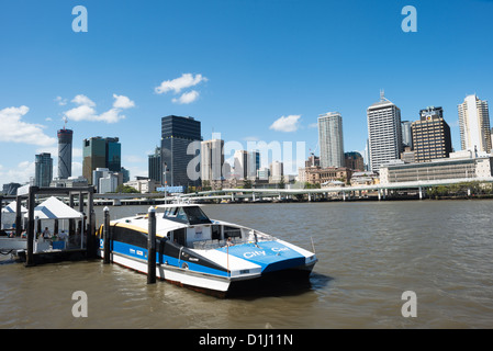 A Citycat ferry pulled up to a ferry terminal at South Bank, with the Brisbane city skyline in the background from - Stock Photo