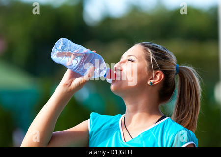 Closeup of a young sportswoman drinking water from bottle - Stock Photo