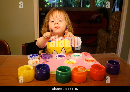 A child paints with her fingers at a table - Stock Photo