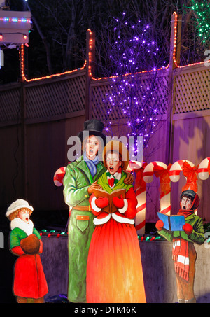 Christmas caroller figurines in front of house lit up for annual Christmas season.-Victoria, British Columbia, Canada. - Stock Photo