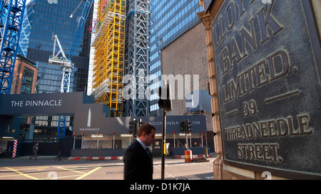View of Pinnacle sign or Bishopsgate Tower construction sit, businessman and Lloyds Bank sign on Threadneedle Street - Stock Photo