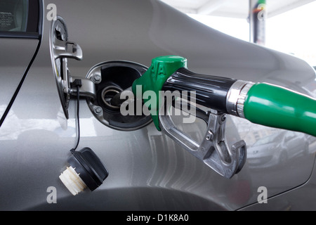 Close up of gas pump nozzle filling up car - Stock Photo