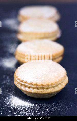 Freshly baked mince pies on a slate serving plate. - Stock Photo