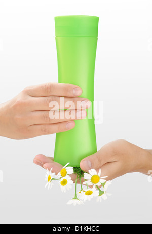 Hands of young woman holding cosmetics bottle and fresh chamomile - Stock Photo