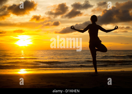 Young woman practicing yoga on the beach at sunset (backlit) - Stock Photo