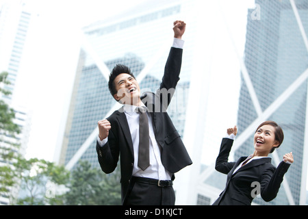Excited business colleagues punching the air outdoors, Hong Kong - Stock Photo