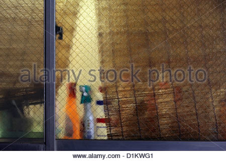 kitchen window with cleaning bottles during night - Stock Photo