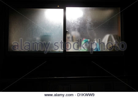 frosted kitchen window with water damp and cleaning products during night - Stock Photo