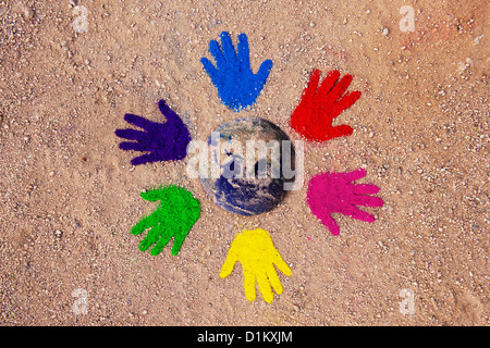 Coloured powder hand prints in a circular pattern on a dirt track with the earth composited in the middle - Stock Photo