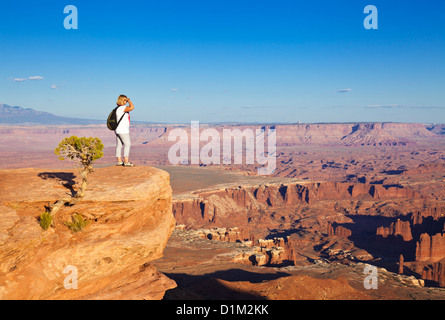 woman hiker standing at Grand View Point overlook  Island in the Sky, Canyonlands National Park, Utah, United States - Stock Photo