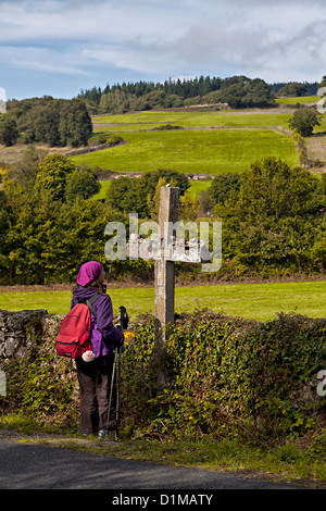 Pilgrim backpacker stops for a moment of silence at the cross, a pilgrimage shrine along the Way of St. James Galicia - Stock Photo
