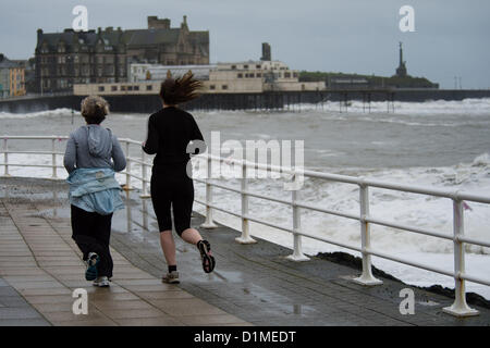 December 29 2012, Aberystwyth Wales UK. Two women jogging along the seafront as high winds and huge waves batter - Stock Photo