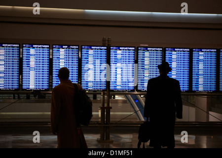 passengers looking at departures board at Denver International Airport Colorado USA - Stock Photo