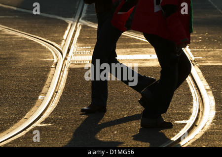 People crossing Railroad Tracks in Back Light in Berlin, Germany - Stock Photo