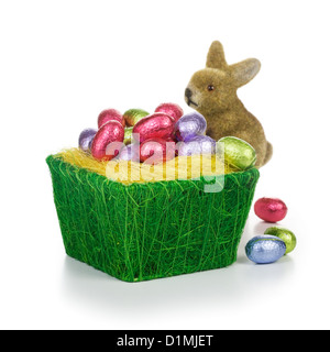 Bunny and basket full of chocolate Easter eggs wrapped in foil on white background - Stock Photo