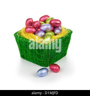 Green basket full of chocolate candy Easter eggs wrapped in foil on white background - Stock Photo