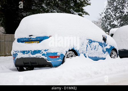 Dormansland, Surrey, England. Parked car on the High Street covered in thick snow after blizzard. - Stock Photo
