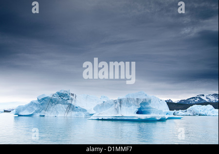 Ice blocks on a lake  under a cloudy sky - Stock Photo