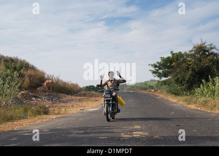 Indian man driving his motorcycle with no hands on the handlebars. India - Stock Photo