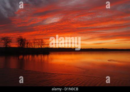 Sunrise over a partially frozen Minnesota lake. - Stock Photo