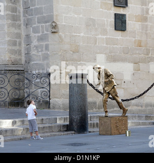 Small boy looking at living statue street entertainer by Seville Cathedral Spain - Stock Photo