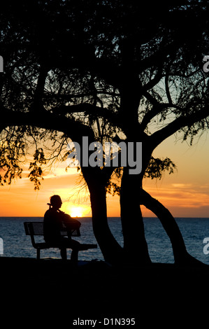 A man plays his guitar as the sun sets at Kamaole Beach Park I on the island of Maui. - Stock Photo