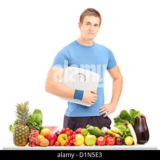 A male athlete holding a weight scale behind a table full of fruits and vegetables isolated on white background - Stock Photo