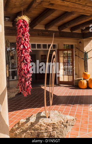 A ristra or string of dried chili peppers hanging outside an art gallery in Santa Fe, New Mexico - Stock Photo