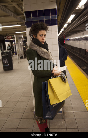 Young woman with a fur collar waits for a subway train in New York City. - Stock Photo